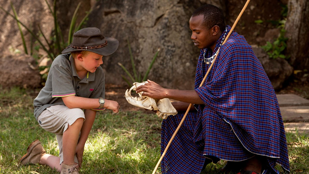 A Maasi guide at the Lodge helps a child—Serengeti, Africa