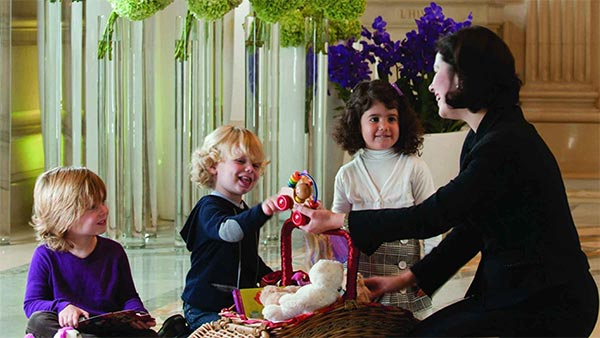 Recreations Manager at Four Seasons Hotel George V, Paris greets three children—Paris, France