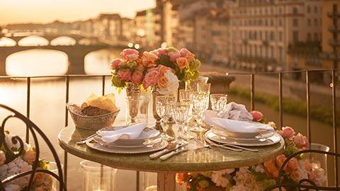En una terraza privada del Ponte Vecchio de Florencia, disfrute de una cena romántica para dos mientras admira la puesta de sol.