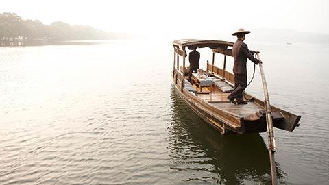 Descubra el fascinante Lago del Oeste mientras admira arquitectura histórica y vegetación exuberante a su llegada al Four Seasons Hotel Hangzhou en una barca tradicional china.