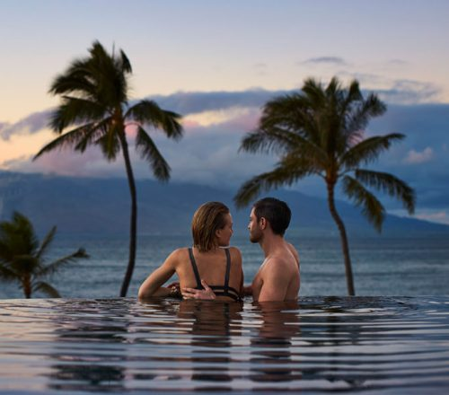 A couple relaxes in the infinity pool at Four Seasons Maui