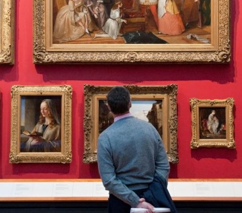 Man looks at paintings in the Victoria and Albert Museum, London, England, UK.