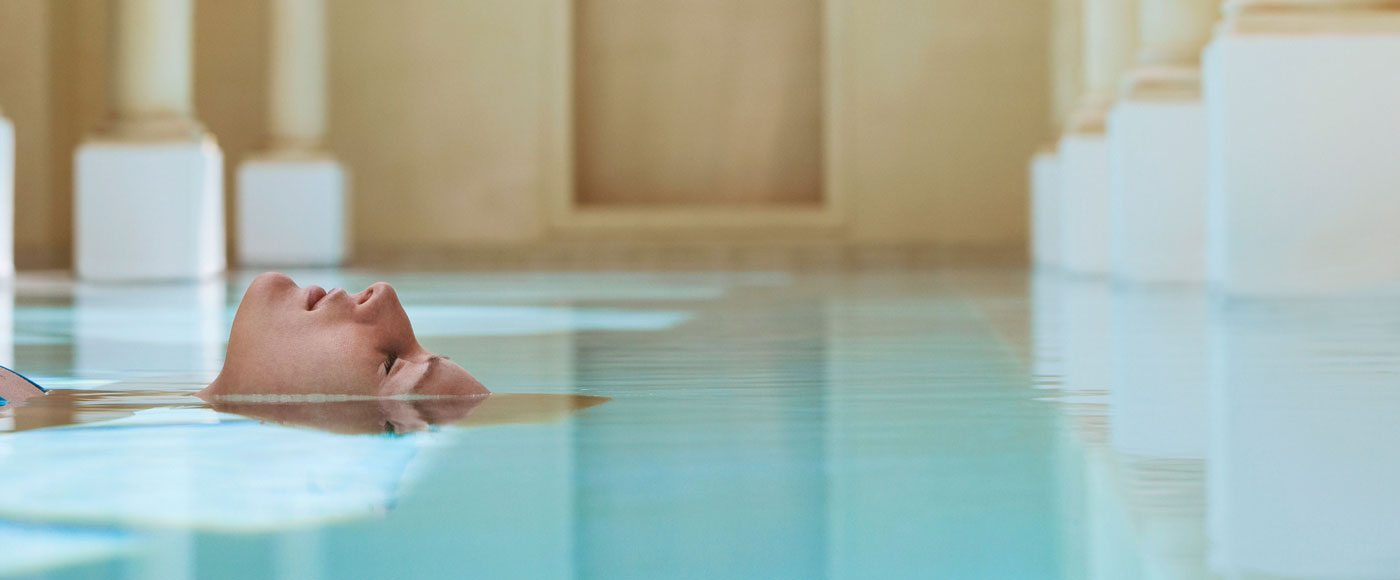 A woman enjoys the water at a public bath.