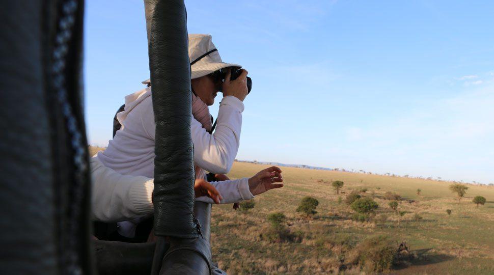 Passenger takes photo on hot air balloon tour in Serengeti