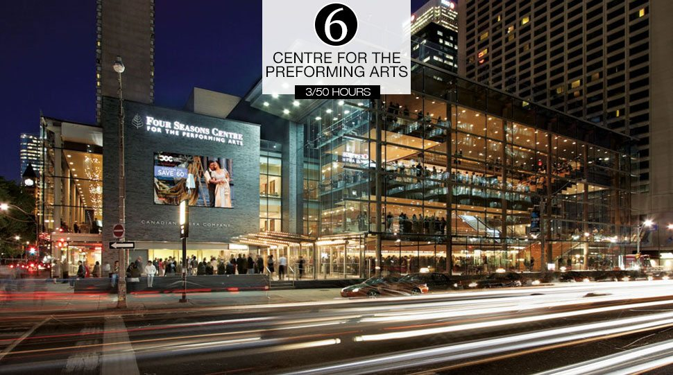 Cars drive by the Four Seasons Centre for the Performing Arts at night.