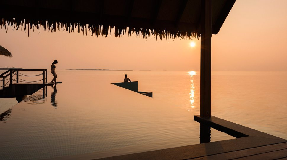 A couple enjoys the infinity pool at Four Seasons Maldives Private Island at Voavah.