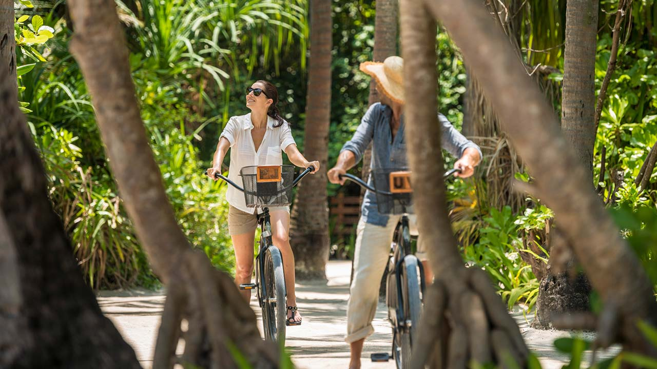 Couple riding bicycles at Four Seasons Resort Maldives