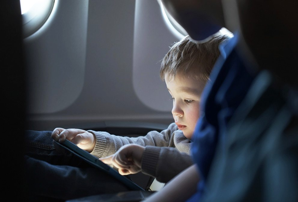 Toddler travelling on airplane watching iPad