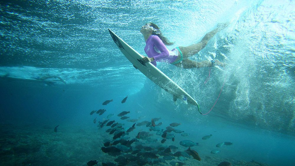 underwater shot of a girl diving beneath a wave with a surfboard