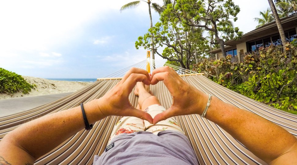 A person making a heart shape with their hands while in a hammock