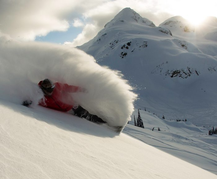 A snowboarder going down a mountain
