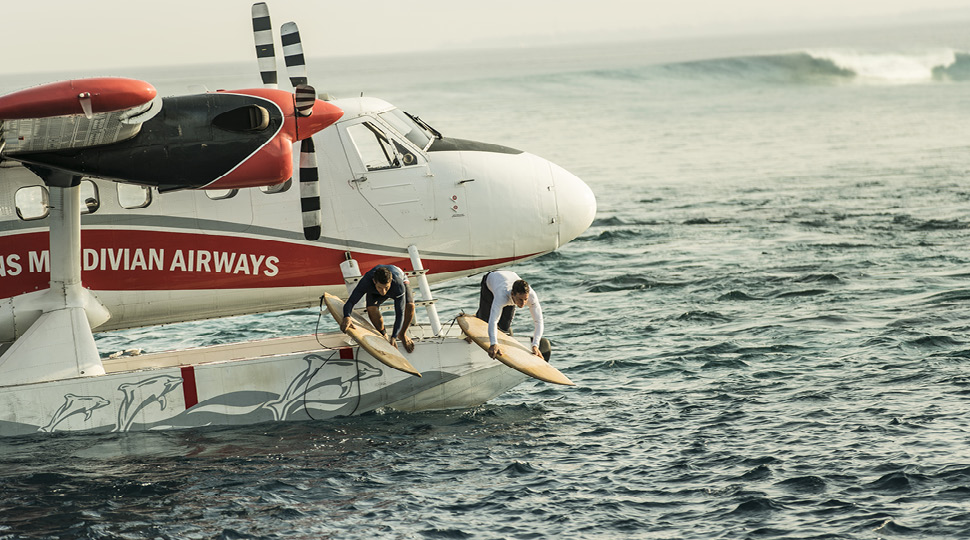 Two surfers dive off of a seaplane into the ocean