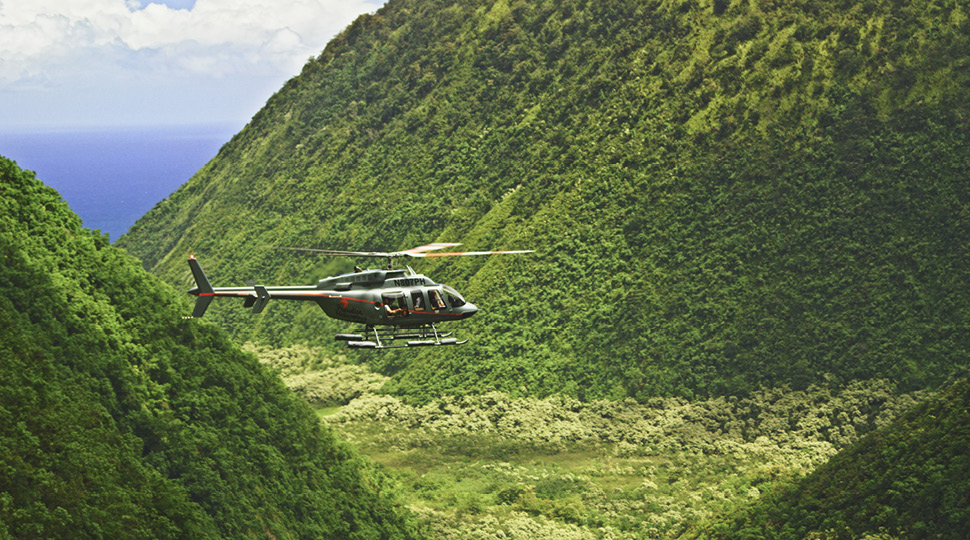A helicopter flies over green peaks in Maui