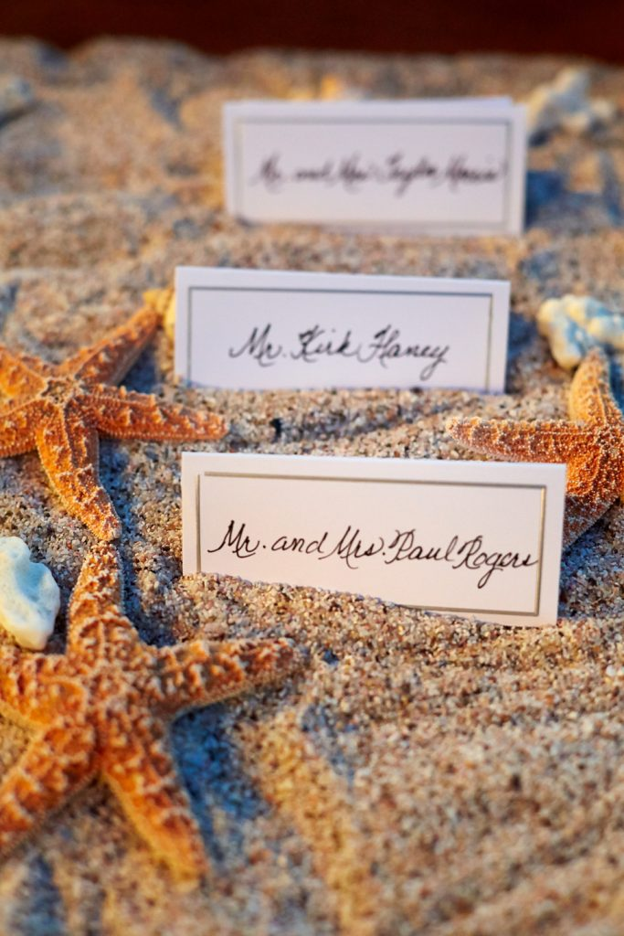 Reception cards on sand with starfish