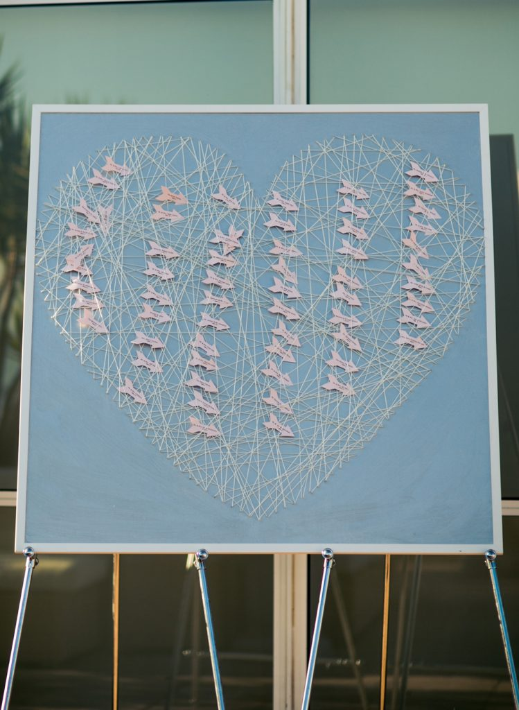 A sign with flowers in the shape of a heart