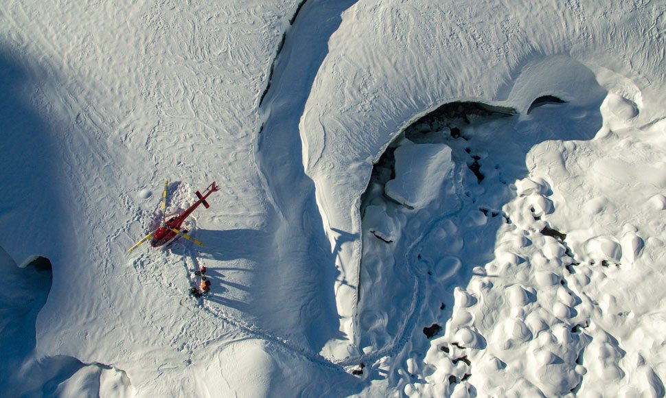 A helicopter landing on a snowy mountaintop in Whistler
