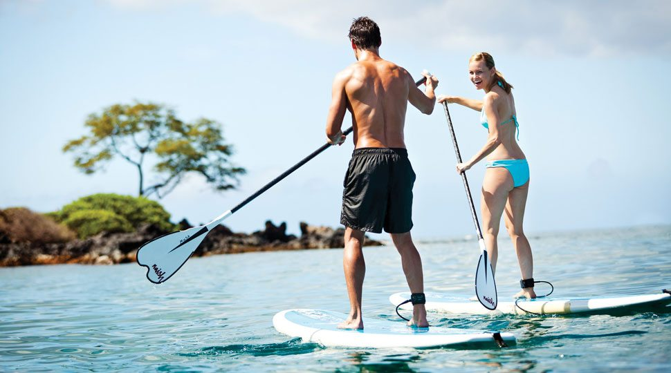 Couple paddleboards in Maui, Hawaii