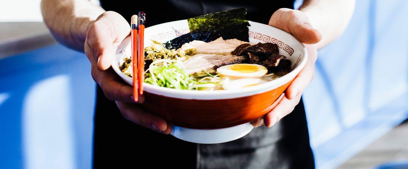 Man holds ramen bowl in Japan