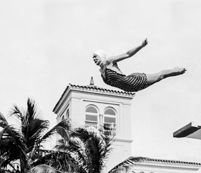 An old photo of a woman diving off a diving board