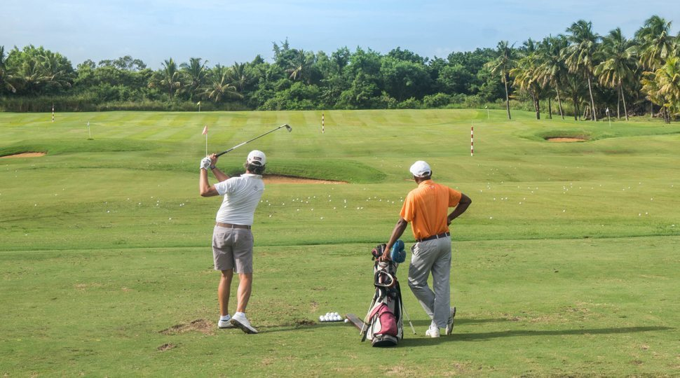 Men play golf at the Four Seasons Mauritius