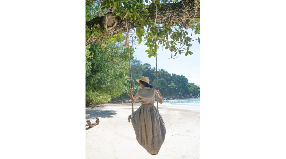 Blogger Marcy Yu swings on a beach at the Four Seasons Seychelles