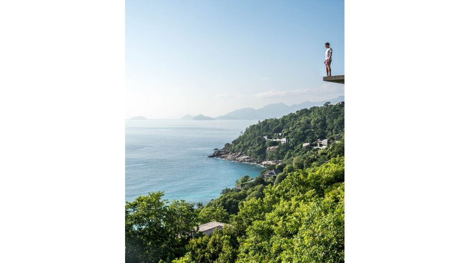 Robert Michael Poole stands on a ledge at Four Seasons Seychelles