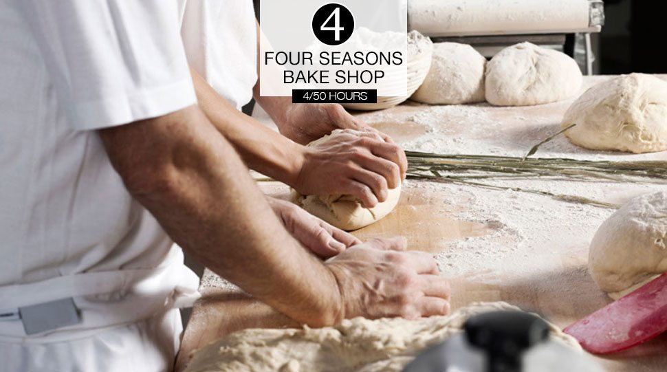 Chefs prepare dough in a kitchen.