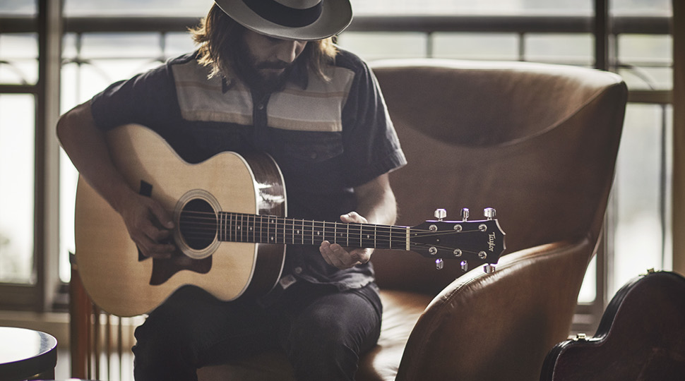 Man in a wide-brim hat plays the guitar in a brown chair