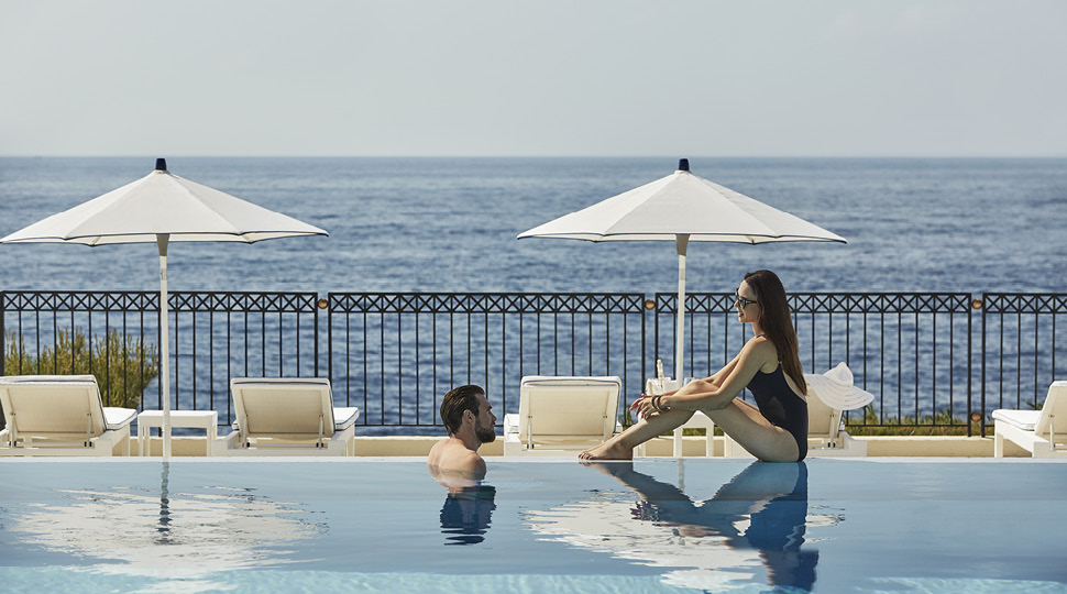 A man and a woman sit on the edge of a pool overlooking the ocean