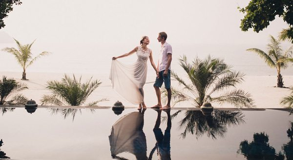 Couple standing by edge of infinity pool
