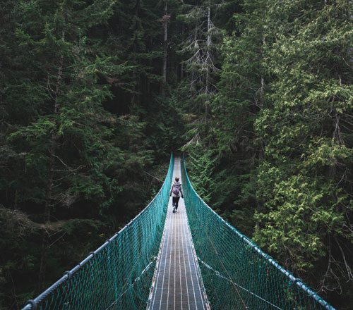 A woman walks across the Capilano suspension bridge in Vancouver, Canada