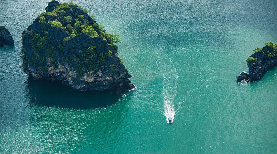 A boat speeds through the waters near Four Seasons Resorts Koh Samui