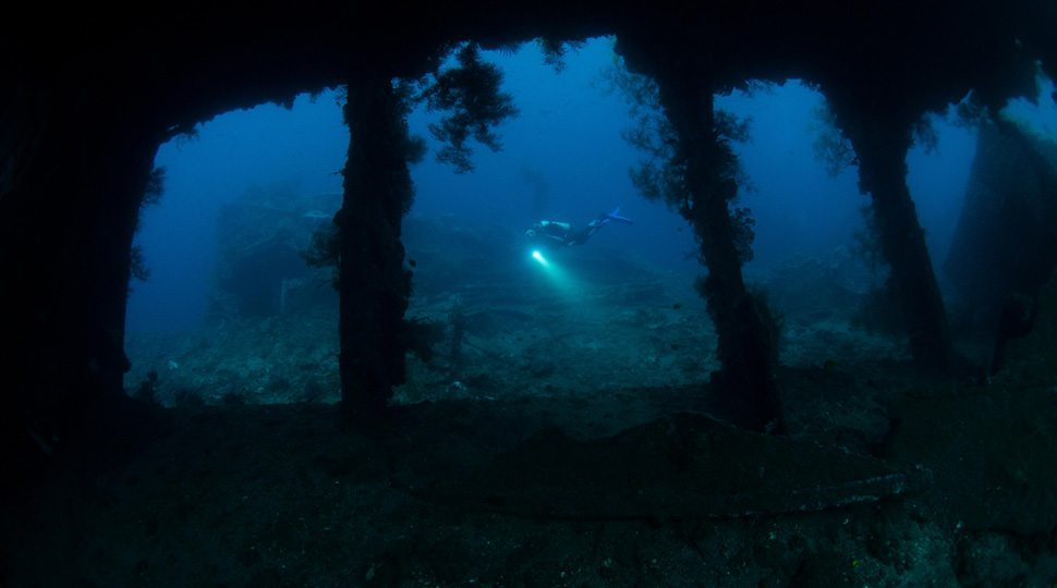 Divers explore a WWII shipwreck of the coast of Bali
