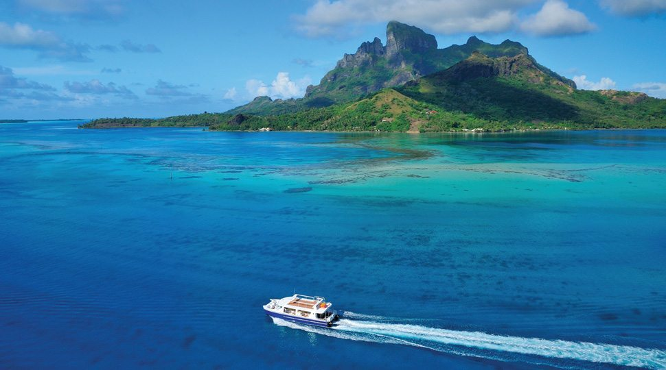 A private boat makes its way around the coast of Bora Bora