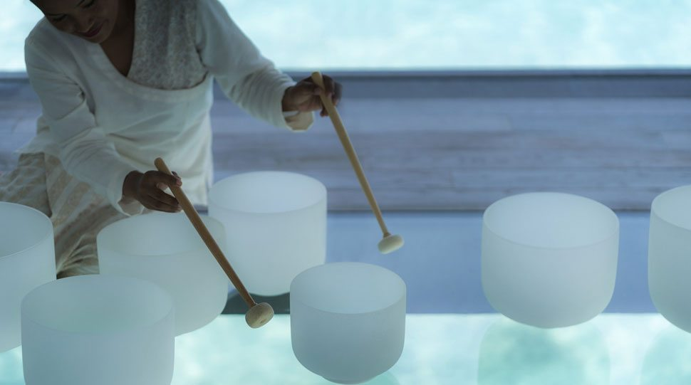 A spa expert at the Four Seasons Maldives provides sound therapy.