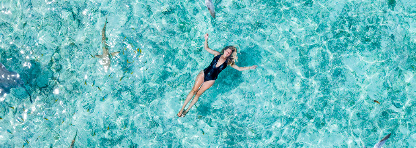A woman in a black bathing suit back-floating in the ocean surrounded by fish