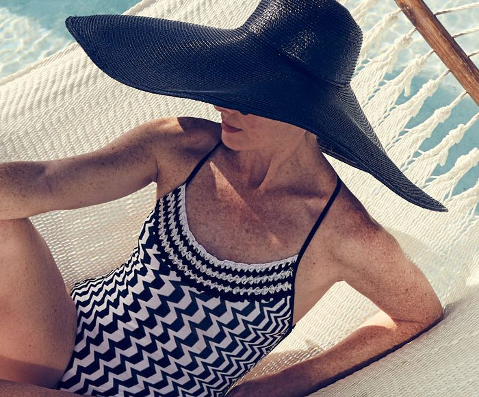 Woman in a black and white abstract print swimsuit and large black sunhat lounges in a hammock