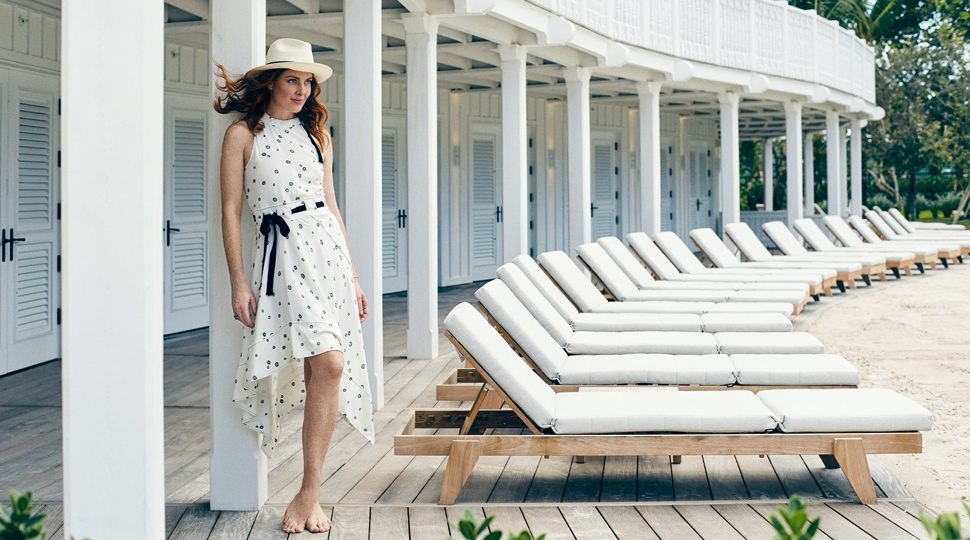 Woman in white polka dot dress and white fedora leans against a large Cabana