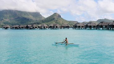 Man rows a boat in the ocean with bungalows in the background