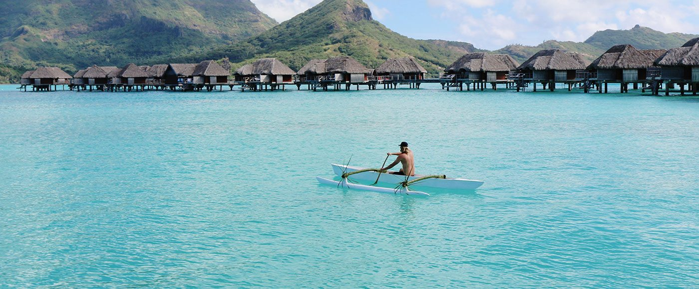 A guest of Four Seasons Resort Bora Bora canoes around the lagoon