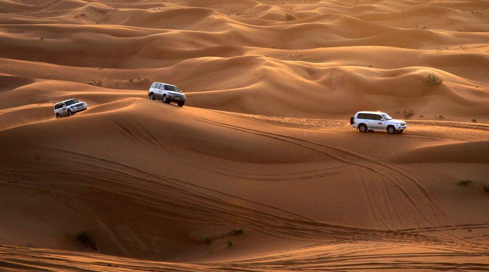 Cars traveling across sand dunes near Dubai