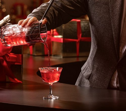 Mixologists pours a holiday cocktail