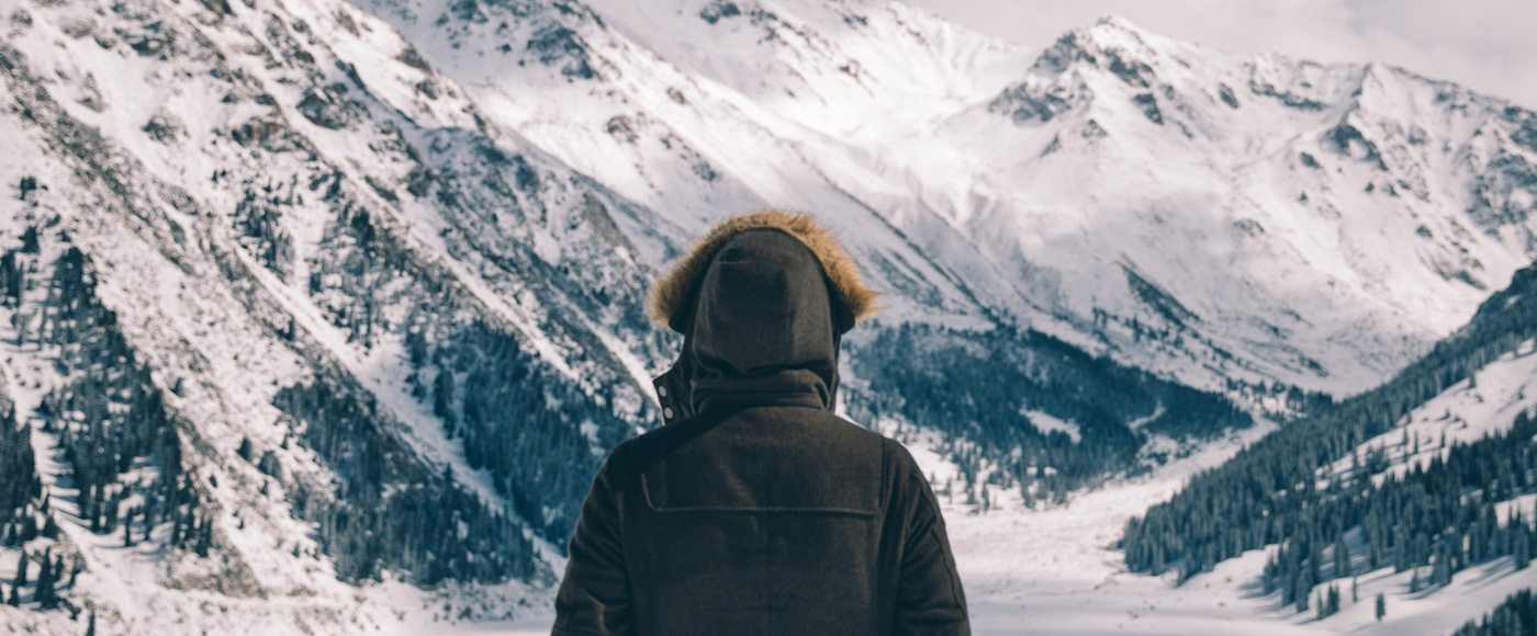 A man looks out over mountain scenery