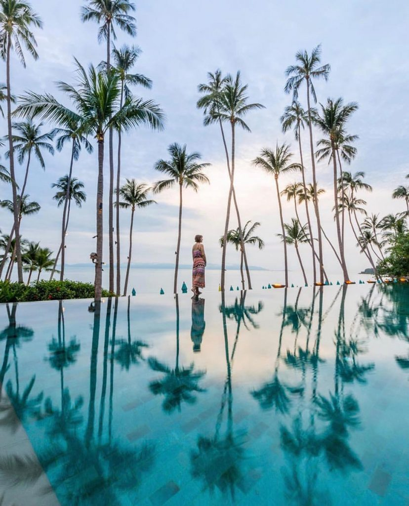 Koh Samui infinity pool with palm trees and woman