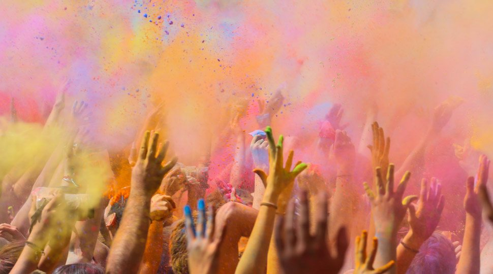 Colorful powders are tossed into the air during Holi.