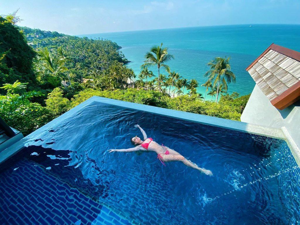 Woman in red bikini back floats in an infinity pool
