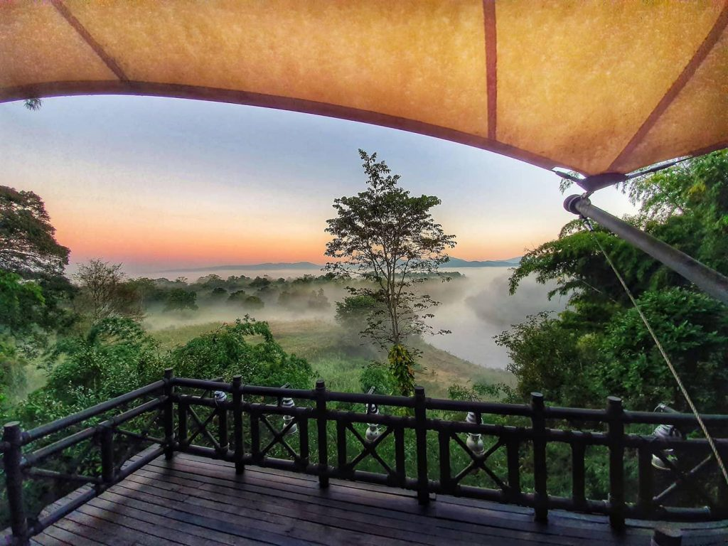 Golden Triangle balcony with view of sunrise and jungle with fog