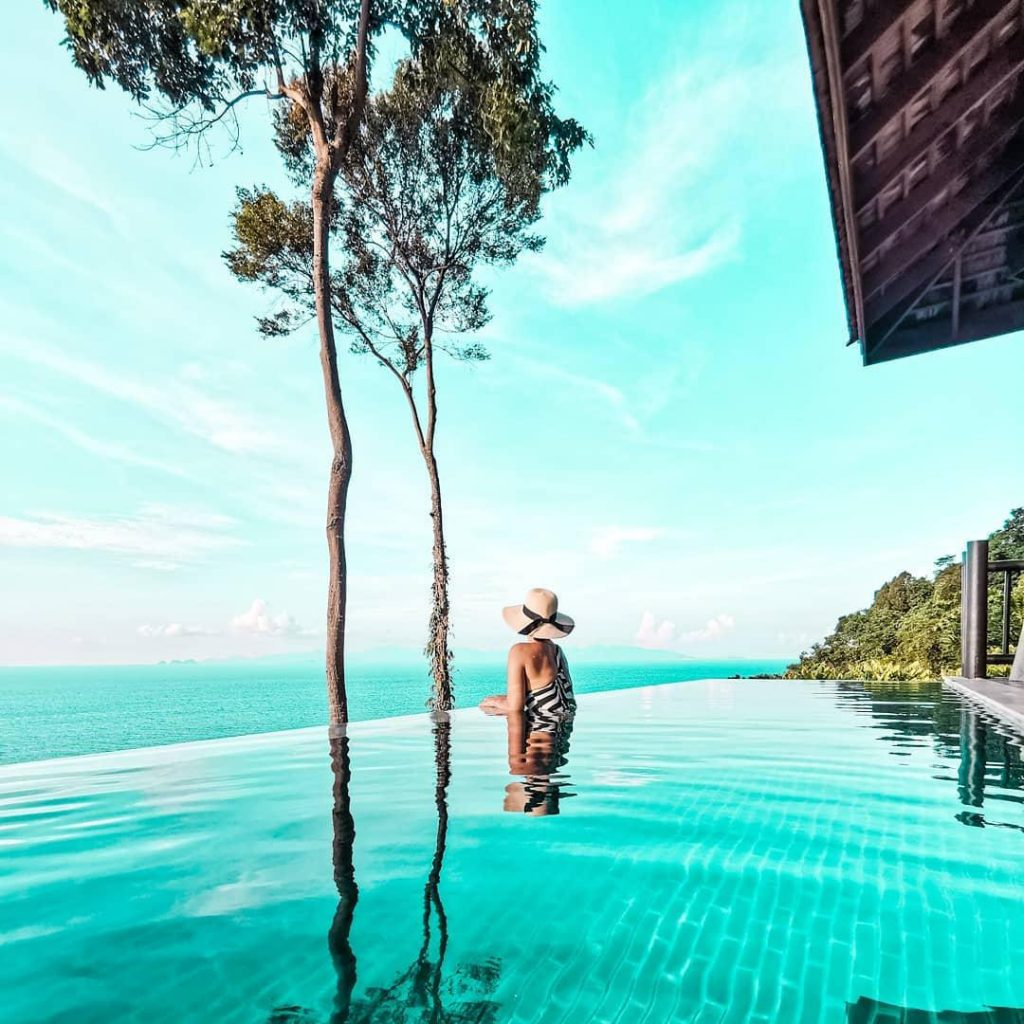 Woman in a wide brim hat lounges on the edge of an infinity pool