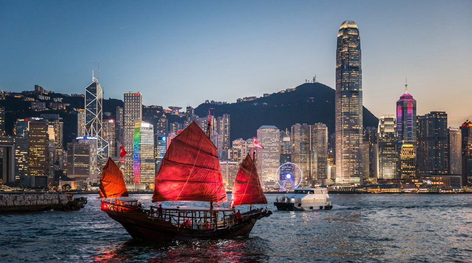 A junk boat sails past the Hong Kong skyline