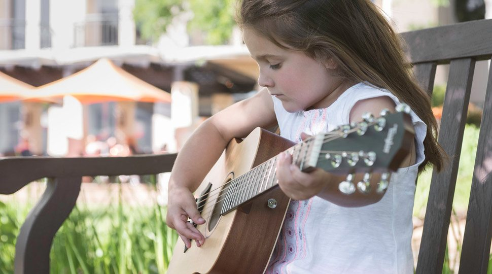 A young girl learns guitar in Austin